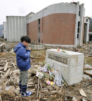 Chlapec sa modlí pri pamätníku obetí ZŠ v japonskom Išinomaki