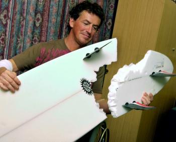 Austrálčan Jake Heron ukazuje zvyšky po žraločích zuboch na svojom surfe