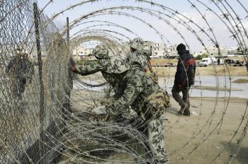 Egyptskí pohraničiari upevňujú ostnatý drôt medzi Egyptom a pásmom Gazy v Izraeli