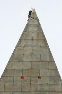 Horolezec pripevňuje laná na vrchol obelisku. Červené body sú signálne svetlá pre lietadlá.