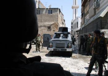 Obrnené vozidlo prechádza zničenými ulicami Damasku