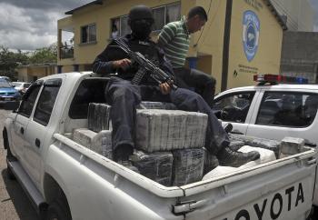 Policajt sedí na časti kokaínu zo zrúteného lietadla