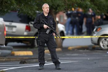 Príslušník SWAT hliadkuje neďaleko bydliska útočníka z kina