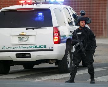 Príslušník policajnej zásahovky hliadkuje pri obydlí vražedného strelca, kým pyrotechnici zneškodňujú nálož