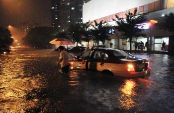 Taxikár opúšťa svoje auto, ktoré uviazlo v zaplavenej ulici