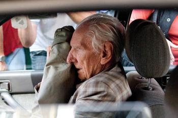 Údajný vojnový zločinec László Csatáry si prikrýva tvár pri odchode z prokuratúry v Budapešti