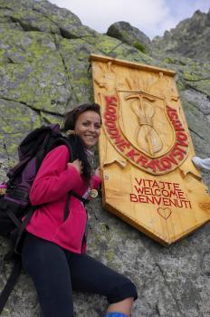 Šarmantná turstika pózuje pred emblémom Slobodného kráľovstva Rysy