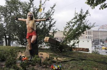 Aktivistka z ukrajinskej feministickej skupiny FEMEN stojí pred  krížom, ktorý spílila na protest proti súdu voči ruskej punkovej skupiny Pussy Riot