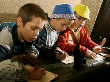 Deti si skúšajú písať diktát pomocou husích bŕk, namáčaných v atramente