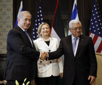 Izraelský premiér Benjamin Netanjahu (vľavo) a palestínsky prezident Mahmúd Abbás si podávajú ruky v prítomnosti šéfky americkej diplomacie Hillary Clintonovej