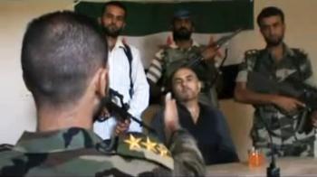 Povstaleckí dôstojník mieri zbraňou na pilota vládnej stíhačky, ktorý sa katapultoval nad povstalcami ovládanom území