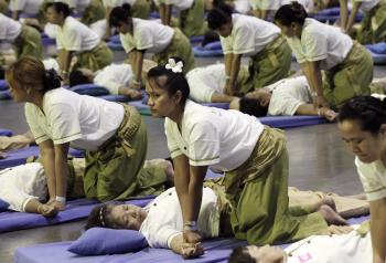 Thajskí maséri počas hromadnej masáže v športovej hale na predmestí Bangkoku