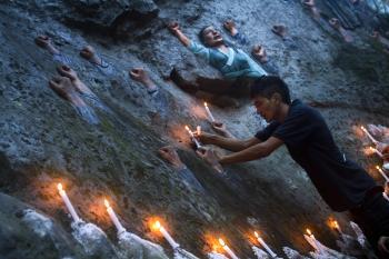 Tibetskí exilanti v Indii kladú sviečku na plastiku známu ako stena tibetských mučeníkov