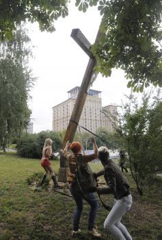 Ukrajinskí podporovatelia Pussy Riot stínajú kríž osadený na počesť obetí politického utláčania
