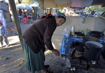 Žena pripravuje  jedlo v provizórnej kuchyni v rómskom tábore
