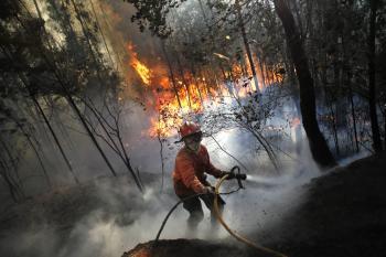 Hasič sa snaží uhasiť oheň v portugalskom Alvaiazere