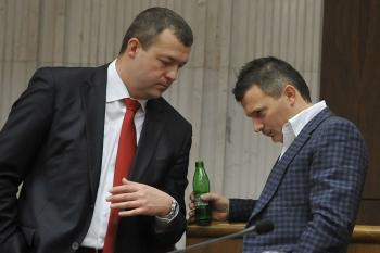 Jaroslav Baška kontroluje obsah fľaše svojeho straníckeho kolegu Jána Počiatka