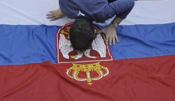 Kosovský Srb bozkáva národnú vlajku počas protestu proti kosovskej nezávislosti