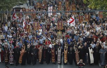Ortodoxných kňazov v procesii nasledujú tisíce ľudí za mier a pokoj v Gruzínsku pred parlamentnými voľbami