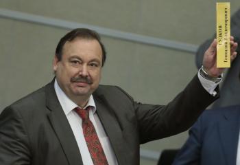 Ruský opozičný poslanec Gennadij Gudkov ukazuje tabuľku so svojím menom počas jeho odchodu