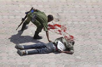 Somálsky vojak sa skláňa nad jedným zo zabitých útočníkov pred hotelom Džazíra