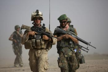 Americký vojak nasledovaný príslušníkmi afgánskych bezpečnostných zložiek