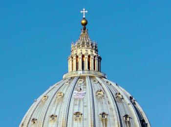 Taliansky podnikateľ Marcello di Finizio stojí na kupole vatikánskej Baziliky svätého Petra  s transparentom Pomoc!!!
