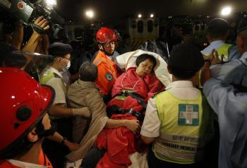 Záchranári prevážajú zachránenú pasažierku po kolízii dvoch lodí