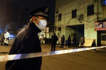 Na snímke čínsky policajt s ochranným rúškom na tvári stráži vstup na trhovisko, kde predstavitelia zdravotných úradov vyraďujú hydinu na utratenie