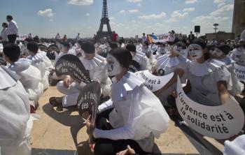 """Demonštranti v kostýme mímov držia transparenty s nápisom """"nie eutanázii u starších ľudí, solidarita je nutná"""" na námestí v Paríži"""