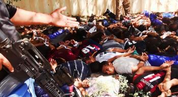 Na snímke bojovníci hnutia Islamský štát v Iraku a Levante (ISIL) so zajatcami