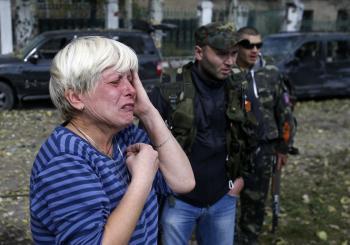 Žena narieka pred zničenou školou po ostreľovaní