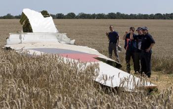 Na snímke vyšetrovatelia prezerajú trosky lietadla Boeing 777