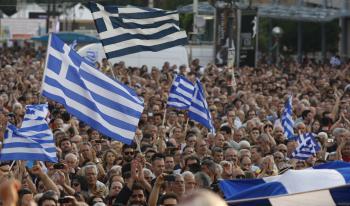 Demonštranti mávajú gréckymi zástavami počas masového protestného zhromaždenia proti úsporným opatreniam gréckej vlády
