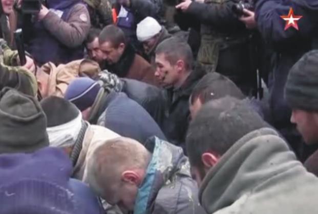 Zajatí ukrajinskí vojaci na kolenách odprosujú obyvateľov Donecka