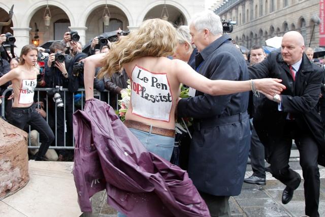 Na snímke tri ženy z feministickej organizácie Femen vyzlečené do pol pása narušili s nacistickými pozdravmi prvomájové kladenie venca šéfky francúzskeho ultrapravicového Národného frontu (FN) Marine Le Penovej