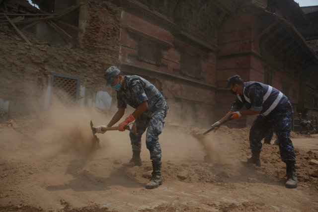 Na snímke nepálski policajti odpratávajú ruiny na Námestí Basantapur Durbar v Káthmandu