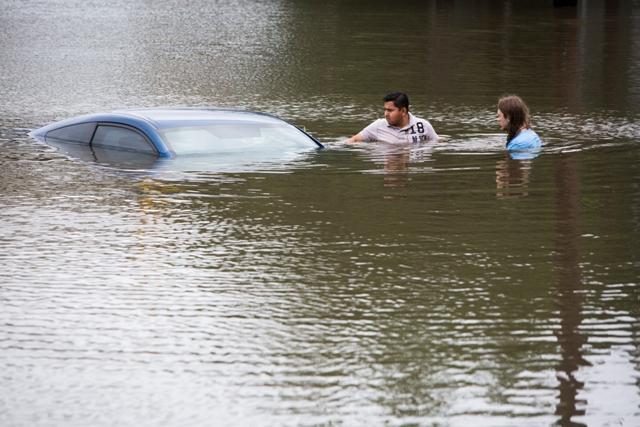 Na snímke potápajúce sa auto na zaplavenej ceste v Houstone, v americkom štáte Texas