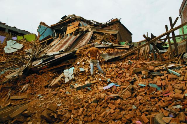 Na snímke muž sa pozerá na zrútený dom po ďalšom zemetrasení v nepálskom meste Čautará v utorok 12. mája 2015