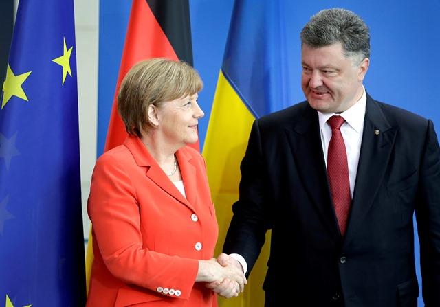 Na snímke nemecká kancelárka Angela Merkelová (vľavo) si podáva ruku s ukrajinským prezidentom  Petrom Porošenkom (vľavo)