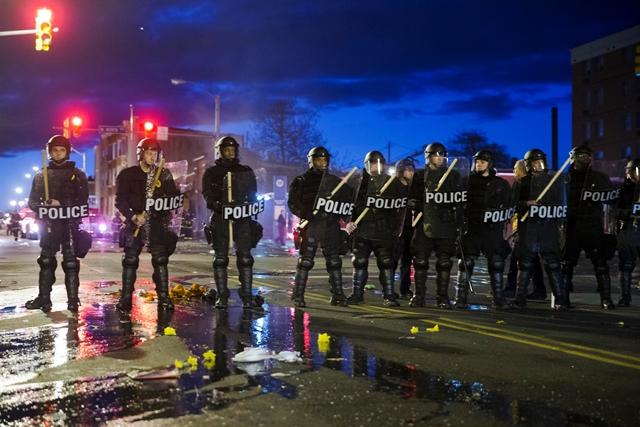 Na snímke policajti hliadkujú počas nepokojov v uliciach Baltimoreu