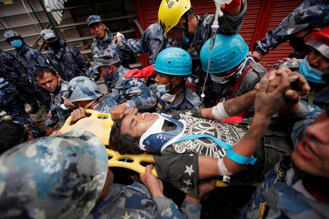 Na snímke záchranári nesú zachraného muža