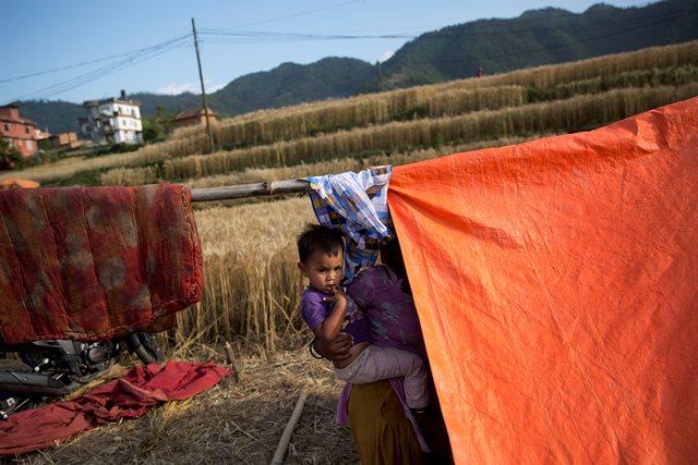 Na snímke nepálska žena drží dieťa v náručí vedľa provizórneho stanu v Nalinchowku pri Káthmandu