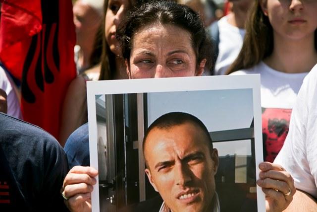 Na snímke žena drží portrét svojho brata, jedného z etnických Albáncov spojených so zrážkami s políciou