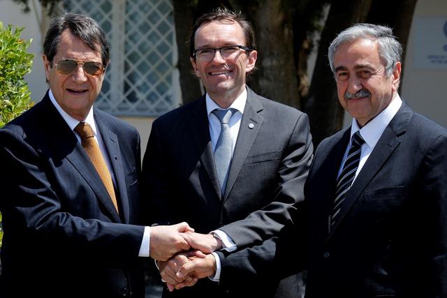 Na snímke cyperský prezident  Nicos Anastasiades (vľavo), líder cyperských Turkov Mustafa Akinci (vpravo) a špeciálny vyslanec OSN Espen Barth Eide (v strede) si podávajú ruky