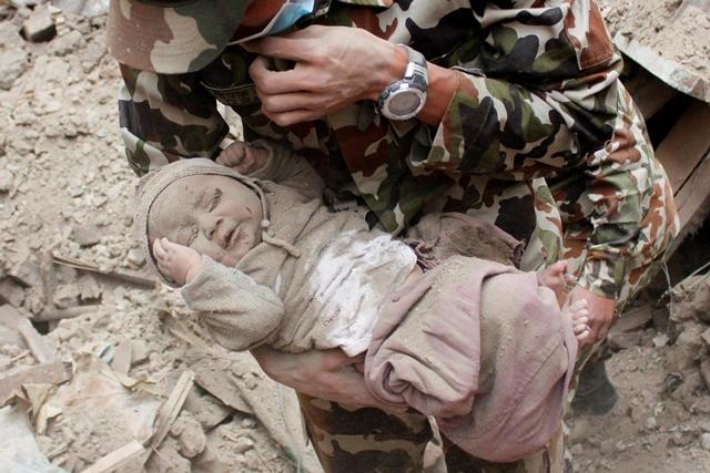 Na snímke nepálsky vojak drží v náručí štvormesačného chlapčeka Sonita Awala, ktorého našli v troskách domu v nepálskom meste Bhaktapur
