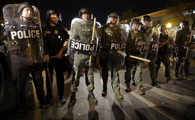 Policajti stoja rozostavaní počas nepokojov v uliciach Baltimoreu