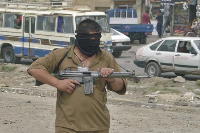 Na snímke hliadkujúci maskovaný ozbrojenec
