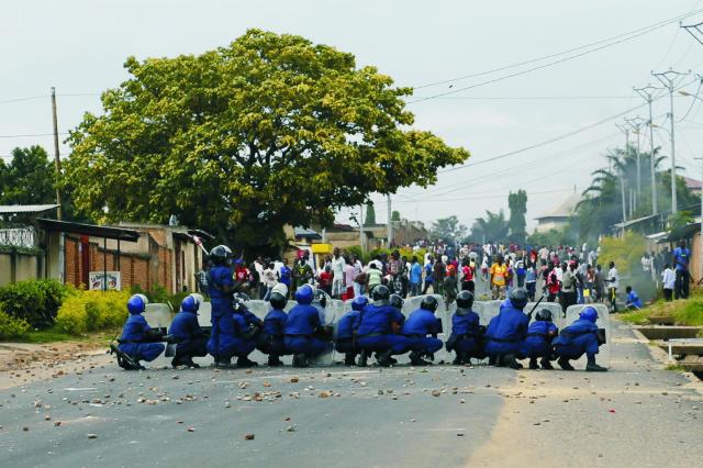 Policajti sa bránia pred kameňmi, ktoré hádžu demonštranti počas nepokojov v burundskej metropole Bujumbura 28. apríla 2015