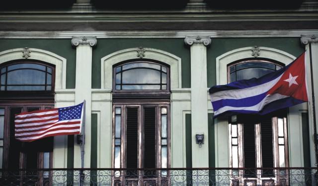 Na archívnej snímke americká a kubánska vlajka vejú na balkóne hotela Saratoga v Havane 19. januára 2015